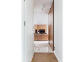 Koncepcja wystroju apartamentu została oparta na bazie koloru drewna (w dwóch różnych odsłonach dla strefy dziennej i nocnej), szarości, bieli i mocnej czerni, ale również granatu i złota, zastosowanego w celu przełamania bazy kolorystycznej. Projekt: Decoroom. Fot. i stylizacja: Marta Behling / Pion Poziom Fotografia Wnętrz