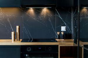 Minimalistyczne, matowoczarne fronty kuchennych szafek oraz płytki imitujące czarny marmur doskonale współgrają z jasnym drewnem blatu. Projekt i zdjęcia: Deer Design