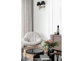 W całym mieszkaniu przede wszystkim postawiono na biel, którą w części dziennej przełamano szarością w postaci kanapy, dywanu, zasłon i poduszek oraz czarnymi elementami – kinkietami, stolikami kawowymi i lampą. Projekt: JT Grupa. Fot. ayuko studio