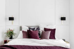 W sypialni rodziców jasnoszarą kolorystykę przełamano kolorowymi dodatkami w postaci bordowych poduszek i narzuty. Projekt: JT Grupa. Fot. ayuko studio