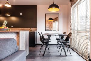 W kuchni dominują ciemne barwy, a całość aranżacji ożywia blask światła rzucanego przez lampy. Projekt i zdjęcia: KODO