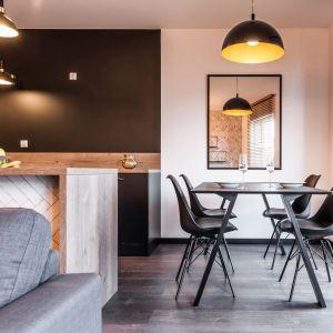 Przestrzeń jadalni została wizualnie oddzielona od kuchni. Zastosowano tu jasną kolorystykę ścian oraz duże lustro, które optycznie powiększa przestrzeń. Projekt i zdjęcia: KODO