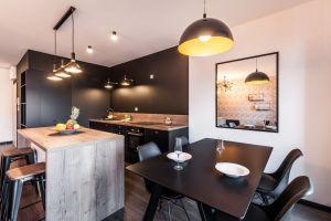 Architekci wykorzystali kolor, by wizualnie wydzielić funkcjonalne strefy pomieszczenia oraz ustalić optyczną granicę między pokojem dziennym i obszarem przygotowywania posiłków. Projekt i zdjęcia: KODO