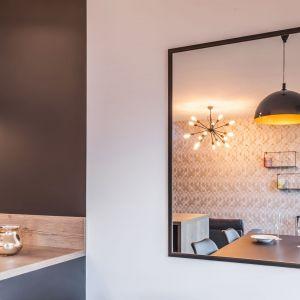 Duże lustro w strefie jadalni optycznie powiększa przestrzeń. Projekt i zdjęcia: KODO