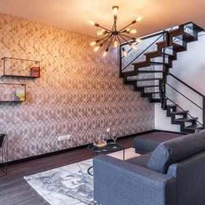 W części wypoczynkowej również dominuje prosta, oszczędna wwyrazie geometria oraz przestrzenne formy. Wśród nich na pierwszy plan wysuwa się konstrukcja utrzymanych w ciemnej kolorystyce schodów i minimalistyczne dodatki. Projekt i zdjęcia: KODO
