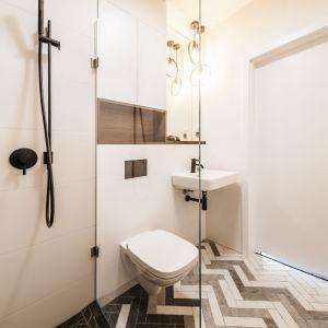 Łazienka współgra stylistycznie z pozostałą częścią mieszkania. Znajdziemy w niej zarówno kontrasty, złożone z bieli oraz różnych odcieni szarości, jak i drewniane akcenty. Projekt i zdjęcia: KODO