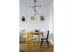 Kącik z okrągłym drewnianym stołem łączy obie strefy i pełni podwójną funkcję – jest miejscem spożywania codziennych posiłków oraz wygodnym aneksem jadalnym w salonie, gdy gospodarze przyjmują gości. Projekt: MADAMA. Fot. Yassen Hristov