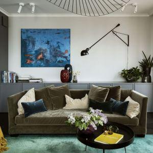 Dużą, oliwkową sofę w salonie zestawiono ze szmaragdowym dywanem i zgrabnymi fotelikami w kolorze wzburzonego morza. Projekt: Katarzyna Arsenowicz. Fot. Yassen Hristov (Hompics)