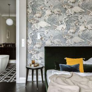 Bohaterem numer jeden jest tutaj duże łóżko obite miękką tkaniną w pięknej zieleni. Stanęło na tle ściany z dekoracyjną tapetą we flamingi. Projekt: Katarzyna Arsenowicz. Fot. Yassen Hristov (Hompics)