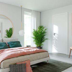 Drzwi wewnętrzne Vector Premium T w kolorze białym, o gładkiej powierzchni skrzydła to doskonałe tło dla barwnych tekstyliów oraz roślin w sypialni. Fot. Porta Drzwi