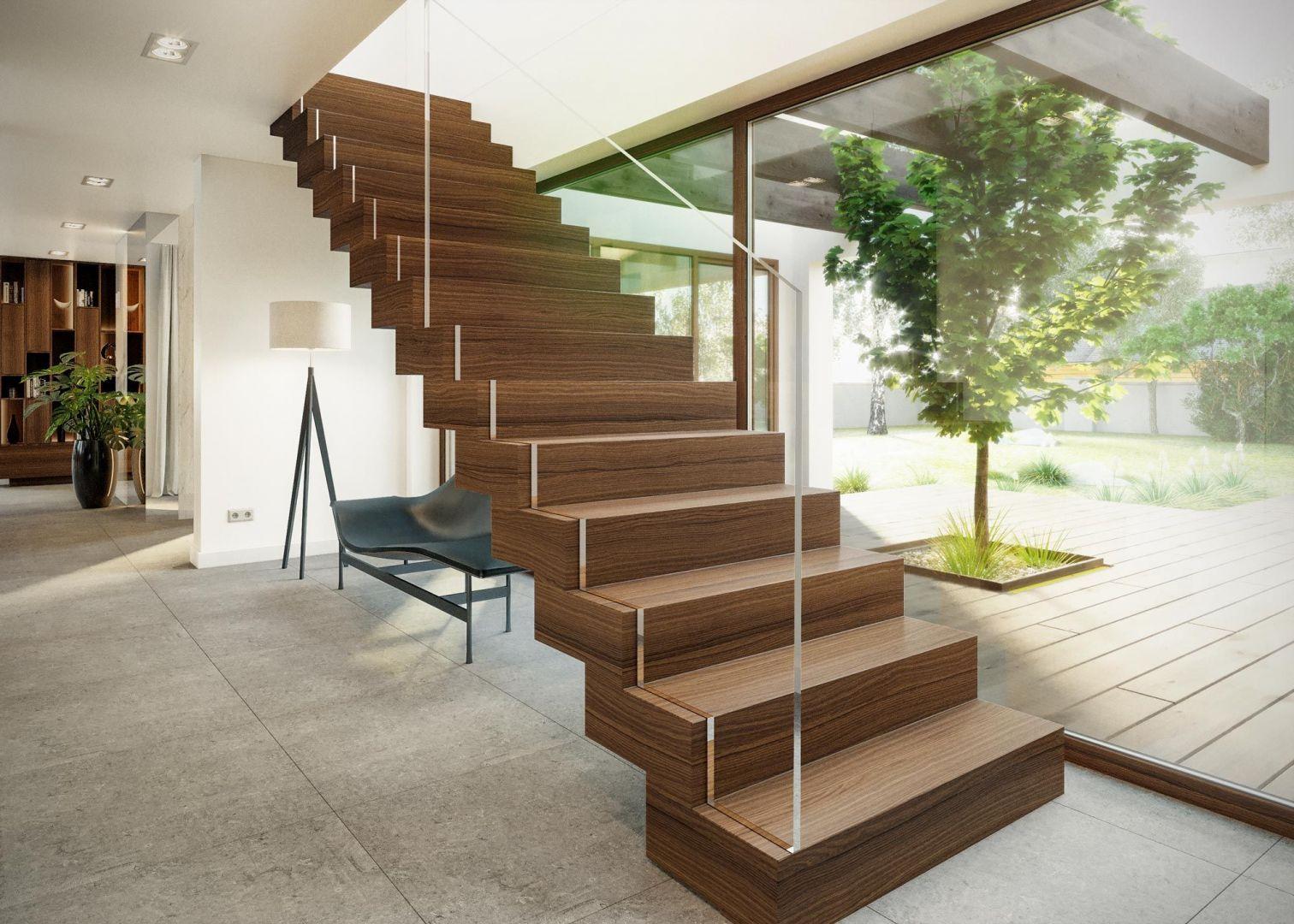 W budynku zaprojektowano schody dywanowe, które zostały ciekawie wyeksponowane na tle dużego, panoramicznego przeszklenia. Dom HomeKoncept 13. Projekt i zdjęcia: HomeKoncept