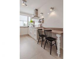 Domowy iprzytulny charakter nadają kuchennemu wnętrzu dodatki – prosta cegiełka na ścianie, uchwyty i frezowane fronty wkomponowanych we wnękę szaf, tradycyjne w formie krzesła oraz stylizowane nogi stołu icokołu. Projekt i zdjęcia: KODO