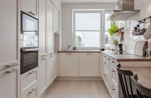 W kuchni dominującą biel przełamuje wzór drewna, w postaci podłogi, blatów ipółek, oraz szarość srebra iczerń, przewijające się w elementach takich jak sprzęt AGD, oświetlenie, detale mebli czyakcesoria. Projekt i zdjęcia: KODO
