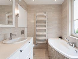 Spójność aranżacyjną utrzymano także w łazience – jasną ceramikę umieszczono wotoczeniu płytek wodcieniu ciepłego i przytulnego beżu. Projekt i zdjęcia: KODO
