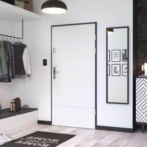 Drzwi wejściowe Kwarc w białym kolorze w oprawie z czarnej ościeżnicy. Fot. Porta Drzwi