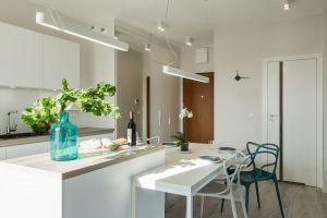W tak skomponowanej przestrzeni, jasnej i stonowanej, wyróżniają się mocniejsze akcenty kolorystyczne – komplet krzeseł z finezyjnymi oparciami, w tym jedno w mocnym turkusie. Projekt i zdjęcia: KODO