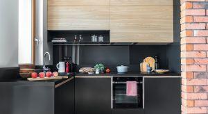 Czarne matowe fronty zestawione z kolorem drewna w jasnym wybarwieniu i czerwoną cegłą na ścianie nadały kuchni w bloku stylowy charakter wnętrza dla mężczyzny. Praktyczne rozwiązania schowane wewnątrz zabudowy – uczyniły ją miejscem idealny