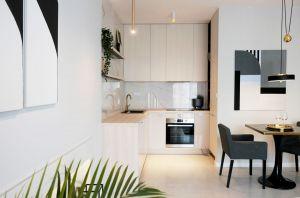 Wysoką kuchenną zabudowę oraz niezbędny sprzęt AGD architektka umieściła we wnęce naprzeciw okna i oddzieliła od salonu fragmentem ściany, tak że jest on niemal niewidoczny. Projekt i zdjęcia: Ania Zbudniewek-Nowicka (Vibo Studio)