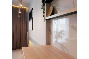 Rezygnacja z górnych szafek na rzecz półek oraz wyłożenie fragmentu ściany marmurem sprawiło, że patrząc od strony wejścia do salonu trudno domyślić się, że jest tutaj kuchnia. Projekt i zdjęcia: Ania Zbudniewek-Nowicka (Vibo Studio)