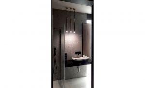 Łazienka to z kolei nowoczesne połączenie czerni, drewna i płytek Terrazzo z klimatycznym oświetleniem w złotych oprawach. Projekt i zdjęcia: Ania Zbudniewek-Nowicka (Vibo Studio)