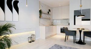 Właścicielka tego dwupokojowego mieszkania ceni sobie dobrej jakości materiały i klasyczne motywy aranżacji wnętrz w nowoczesnej odsłonie. Architektka postawiła więc na marmur, granit, złoto, czerń oraz biel, doskonale wyważając proporcje.