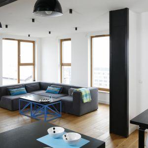 Duża, ciemnoszara kanapa to jedyny mebel w wypełniający domową strefę wypoczynku. Salon nie jest nudny dzięki otwarciu reszty mieszkania, oraz drewnianym ramom okiennym, które z powodzeniem zastępują dekoracyjne dodatki. Projekt: Monika i Adam Bronikowscy, Fot. Bartosz Jarosz