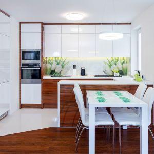 9A&K - meble kuchenne wykończone białymi frontami w połysku doskonale równoważy drewno. Dostępne w ofercie firmy A&K Kuchnie. Fot. A&K Kuchnie
