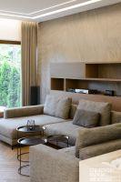 W salonie uwagę zwraca ściana za wygodną sofą, w całości wykończona kamiennymi płytami, których kolor doskonale współgra z drewnianym parkietem ułożonym w klasyczną jodełkę. Projekt: Czajkowski Kuźniak Architekci. Fot. Archifolio / Tomasz Zakrzewski