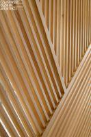 Kompozycja drewnianych lameli tworzy ażurową ściankę oddzielającą salon od korytarza. Projekt: Czajkowski Kluźniak Architekci. Fot. Archifolio / Tomasz Zakrzewski