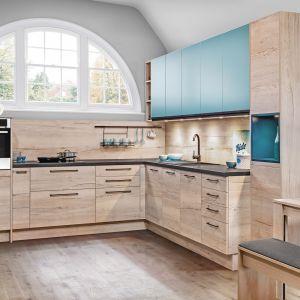 Zabudowę kuchenną z przewagą dekorów drewna można ożywić intensywnym akcentem kolorystycznym, ciekawie wkomponowanej  w bryłę mebli z systemu KAMplus. Fot. KAM