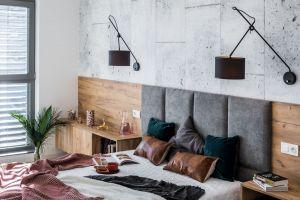 Zestawienie na jednej ścianie zimnego betonu i ciepłego drewna sprawia, że pomieszczenie jest jednocześnie surowe i przytulne. Projekt i zdjęcia: KODO