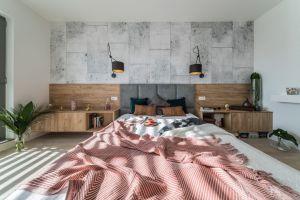 Punktem centralnym wtak dużej przestrzeni jest obszerne łóżko zszarym, pikowanym zagłówkiem, wkomponowane w oryginalną zabudowę umieszczoną na całej długości ściany. Projekt i zdjęcia: KODO