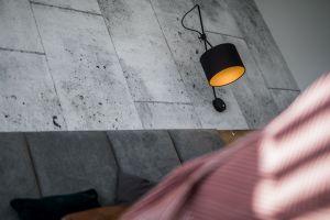 Ciepła dodaje wnętrzu oświetlenie wpostaci dużych, regulowanych lamp ściennych, zamontowanych nad wezgłowiem łóżka. Projekt i zdjęcia: KODO
