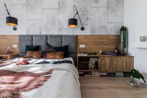 Minimalistyczny styl sypialni przełamują dodatki: wzorzysta narzuta, poduszki wykonane zaksamitnych, strukturalnych tkanin oraz tłoczonej skóry – materiału korespondującego kolorystycznie zzabudową. Projekt i zdjęcia: KODO