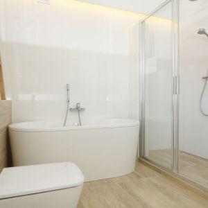 Ta łazienka zachwyca prostotą i ciepłem. Wanna postawiona przy samej ścianie nie ogranicza przestrzeni. Projekt: Joanna Ochota. Fot. Bartosz Jarosz