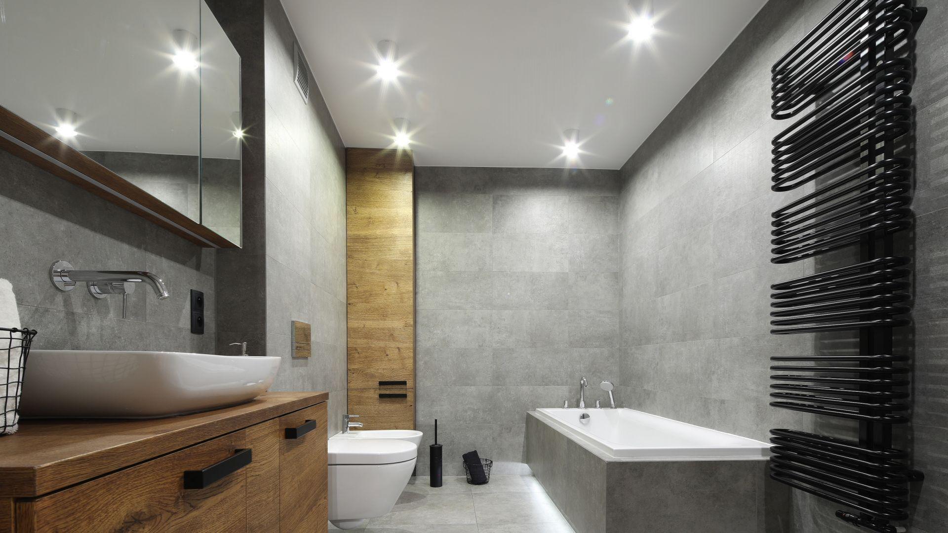 Nowoczesna, szara łazienka nie jest zimna dzięki drewnianym elementom wykończenia. Zabudowana wanna idealnie komponuje się z minimalizmem koloru i formy. Projekt: Katarzyna Walawska. Fot. Bartosz Jarosz