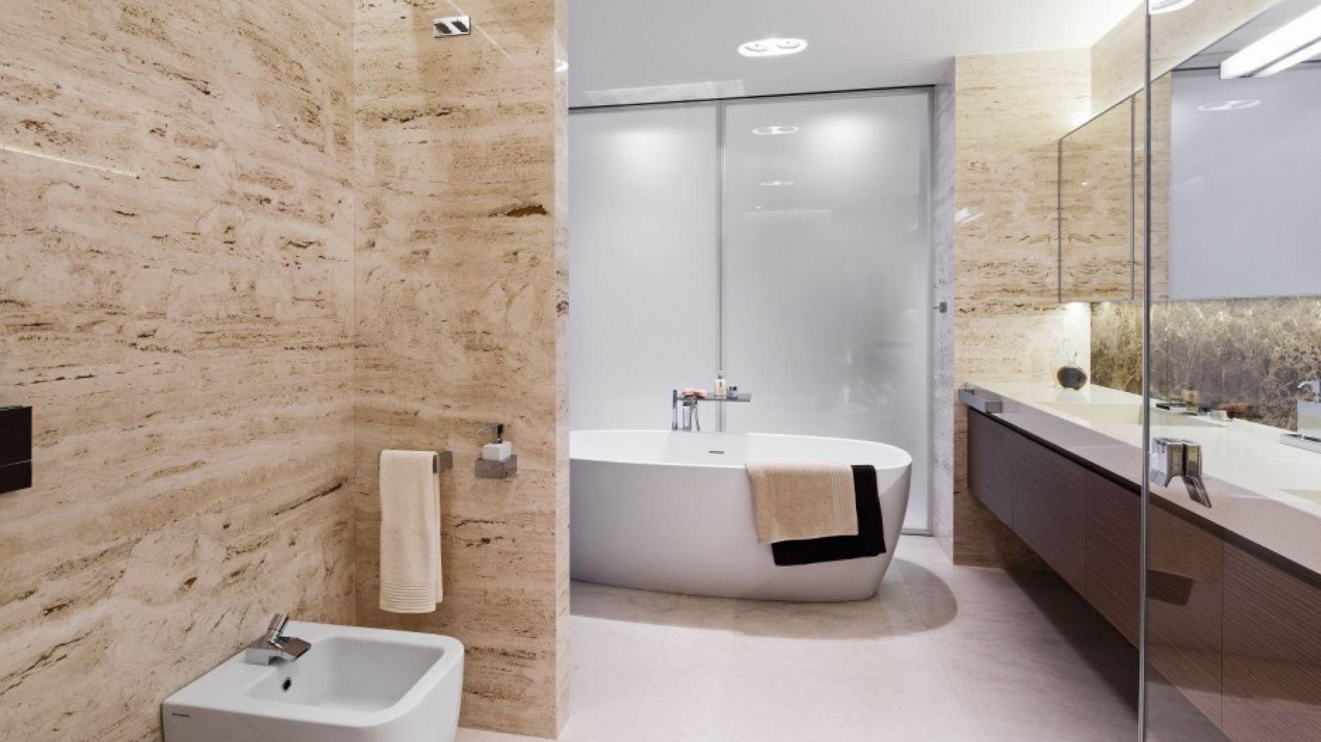 Duża wanna to wygodne rozwiązanie kąpielowe w przestronnej łazience. Kamienne ściany nie wyglądają zbyt ciężko dzięki piaskowej barwie. Projekt: Anna Fodemska. Fot. Bartosz Jarosz