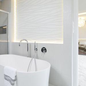 Łazienka przy sypialni wygląda niezwykle lekko, dzięki ozdobnej dekoracji ze światłami umieszczonej nad wanną.  Projekt: Agnieszka Hajdas-Obajtek. Fot. Bartosz Jarosz