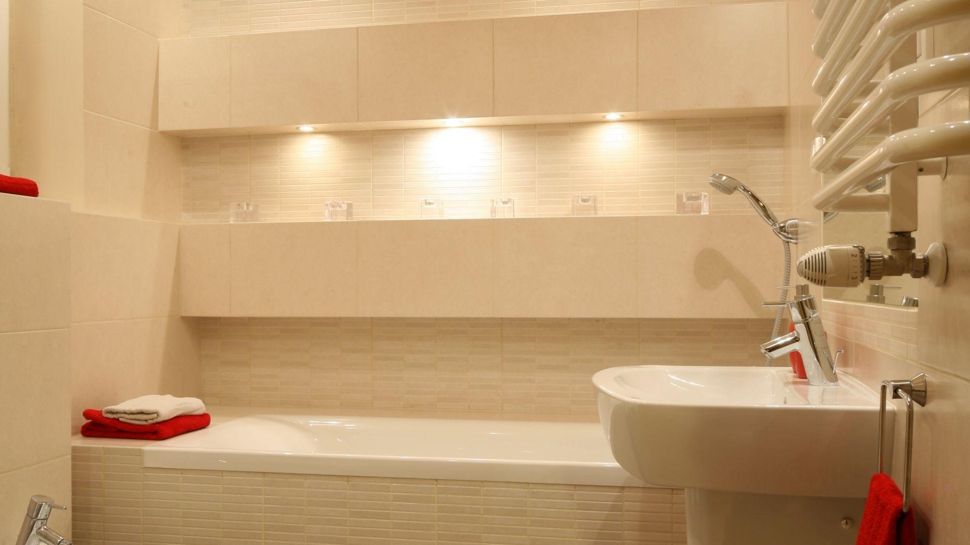 Wanna dobrze wygląda w tak małej łazience, dzięki zastosowaniu neutralnej kolorystyki, ozdobnych półek i odpowiedniego oświetlenia. Kolorowe dodatki ożywiają jednolite wnętrze. Projekt: właściciele. Fot. Bartosz Jarosz