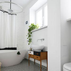 Niewielka łazienka zaprojektowana została oryginalni i z pomysłem. Wolnostojącą wannę połączono z prysznicem w niebanalny sposób. Takie rozwiązanie zapewnia komfort użytkowania. Projekt: Maria Biegańska. Fot. Bartosz Jarosz