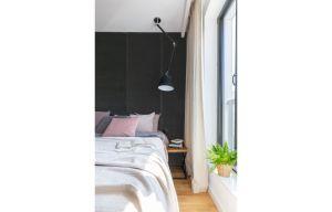 Obita grafitowym aksamitem ściana współgra z dekoracją łóżka, którego proste nakrycie wraz z poduszkami utrzymano w tonacji szarości, grafitu, subtelnego wrzosu i różu. Projekt i zdjęcia: Decoroom