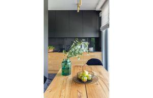 Pozornie ascetyczna kuchnia otwarta na korytarz i salon łączy subtelność matowych powierzchni oraz kuchenne fronty wykonane z forniru imitującego naturalne drewno. Projekt i zdjęcia: Decoroom