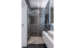 Kabina prysznicowa ze szklanym frontem i ciekawe, nowoczesne oświetlenie nadają  pomieszczeniu interesującą surowość w świeżym wydaniu. Projekt i zdjęcia: Decoroom
