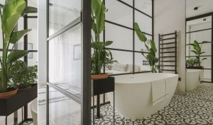W sypialnizdecydowano się umieścić przeszkloną łazienkę z białą wanną iwzorzystymi cementowymi kaflami podłogowymi.  Projekt i zdjęcia: STUDIO.O. organic design