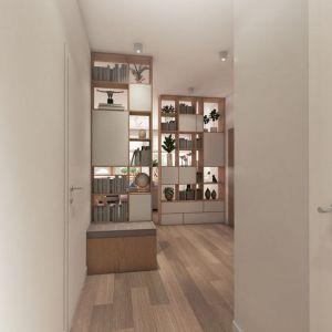 Aby strefa dzienna była jak najbardziej obszerna, właściciele tego mieszkania zdecydowali się otworzyć salon nie tylko na kuchnię, ale i  na przedpokój. Na granicy tego pomieszczenia z kuchnią i jadalnią postawiono ażurowe regały (przy jednym zbudowano ławeczkę ze schowkiem na buty), które zasłaniają okolicę drzwi wejściowych, zapewniają dużo miejsca na książki i różne drobiazgi, nie ograniczając zarazem przestrzeni.