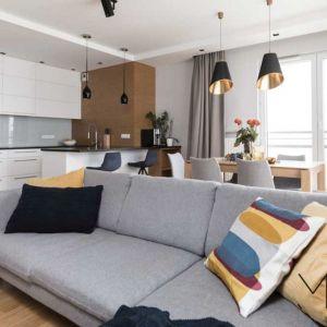 Szczypta kolorów. Stój jadalny w bezpośrednim sąsiedztwie kuchni, a w dalszej części pomieszczenia kąt wypoczynkowy z sofą, która stoi do nich plecami – to najlepszy pomysł na rozmieszczenie różnych funkcji w niewielkiej przestrzeni dziennej.