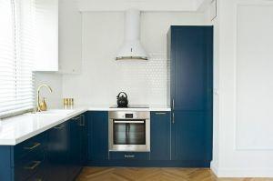 Granatowa zabudowa kuchni to najmocniejszy barwny akcent w części dziennej. Projekt: Magdalena Miśkiewicz. Zdjęcia: Anna Powałowska