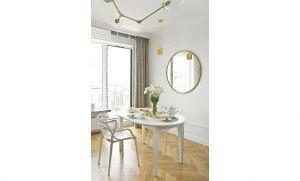 Pomiędzy kuchnią a częścią wypoczynkową projektantka ulokowała jadalnię, w której stanął biały, owalny stół i nowoczesne krzesła. Projekt: Magdalena Miśkiewicz. Zdjęcia: Anna Powałowska