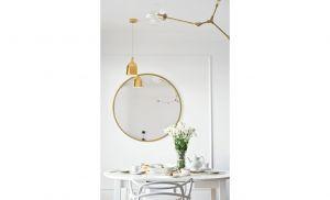 Okrągłe lustro w złotej ramie powiększa przestrzeń i wraz ze złotą oprawą prostej, sufitowej lampy pięknie odbija światło. Projekt: Magdalena Miśkiewicz. Zdjęcia: Anna Powałowska