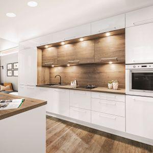Nawet decydując się na dwa rzędy modułów szafek i zabudowę całej szerokości ściany, możemy uatrakcyjnić bryłę mebli poprzez połączenie różnych dekorów na frontach, na przykład wyjątkowo efektownego zestawienia połyskującej bieli i ciepłego rysunku drewna. Fot. KAM